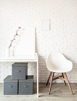 흰색 벽돌 벽 바탕에 테이블에 목화 분기와 포스터 프레임을 비웃는 다. 공간 복사