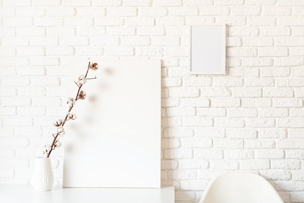 흰색 벽돌 벽 바탕에 목화 분기와 포스터 프레임을 비웃는 다. 공간 복사