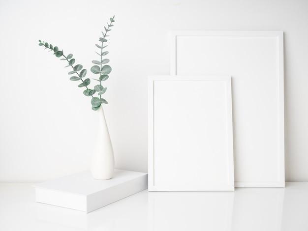 흰색 테이블에 현대 세라믹 꽃병에 유칼립투스 잎 포스터 프레임 책 장식을 모의