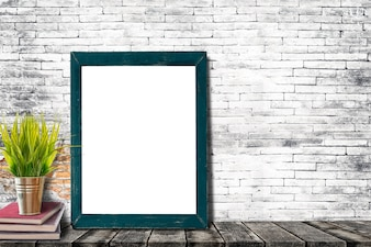 Mock up poster or photo frame with books and houseplant on old wooden table