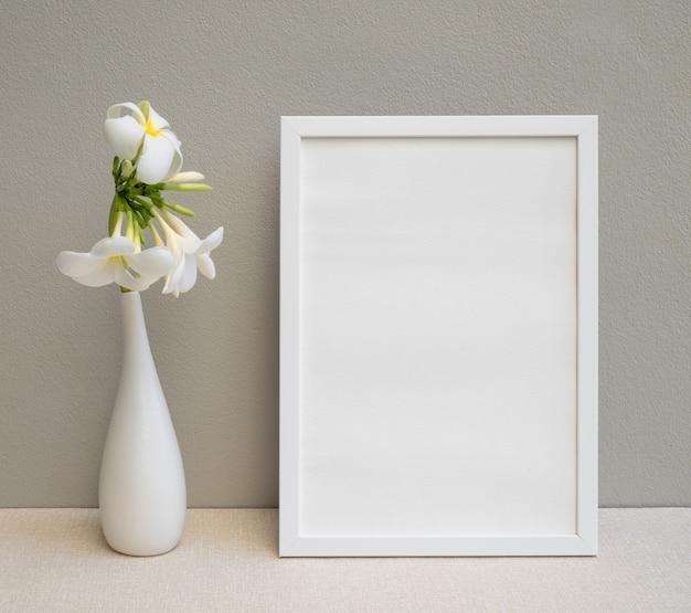 베이지 색 테이블에 현대 흰색 꽃병에 포스터 흰색 프레임과 아름다운 plumeria 또는 frangipani 열대 꽃을 모의