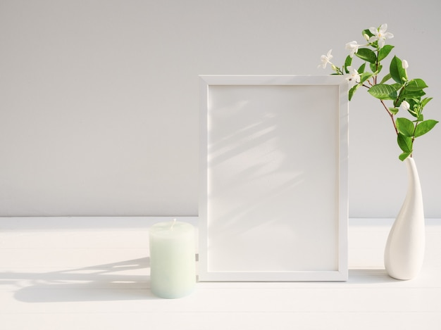 Mock up poster white frame and beautiful gardenia tropical floral in modern white vase decor with green candle on beige table and cement wall surface with long shadow