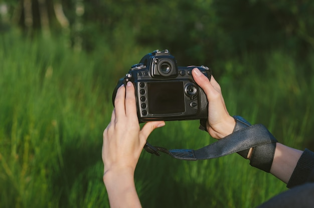 Mock up of a professional photo-video camera in the hands of a girl. against the background of green nature.