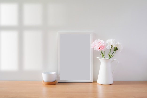 Mock up protrait photo frame with flowers on table