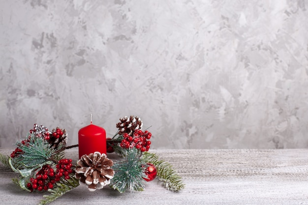 Mock-up of red christmas candle and a wreath of christmas tree branches, cones, red berries