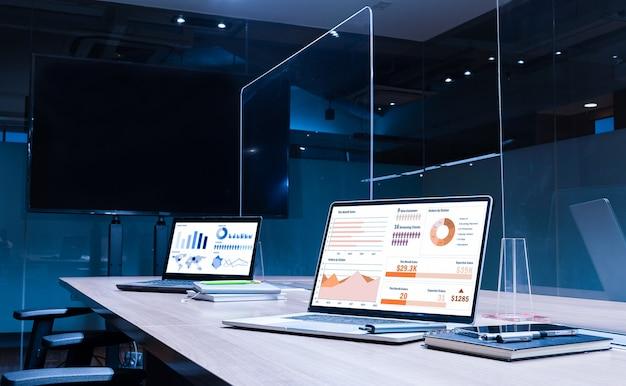 透明なアクリルシートを備えたテーブル上の2台のディスプレイラップトップでのモックアップ販売概要スライドショープレゼンテーションは、会議室でcovid-19を防ぐために、会議テーブルの中央を分離します