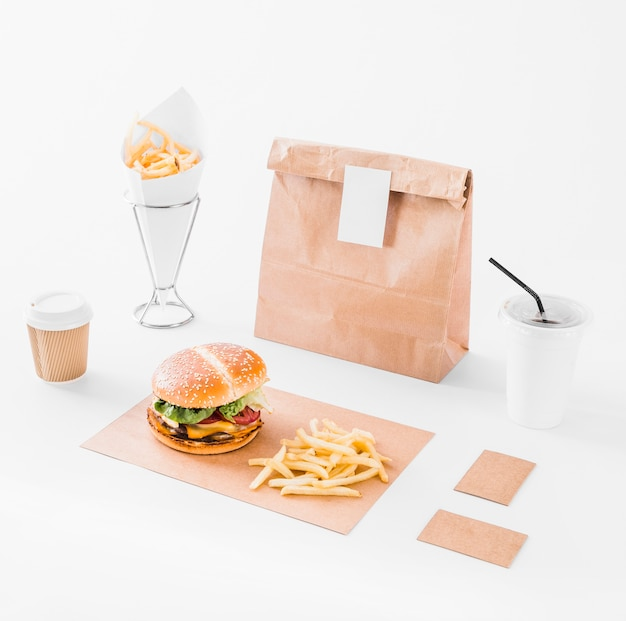 Mock up set of burger; french fries; parcel and disposal cup on white surface
