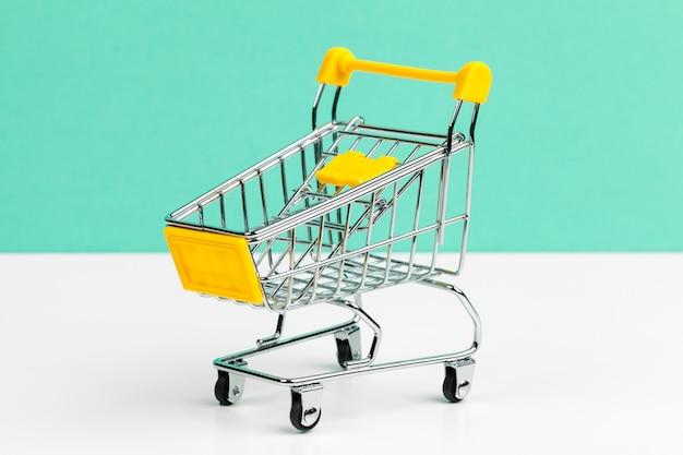 Mock up shoppong online cart on desk table office soft blue wall