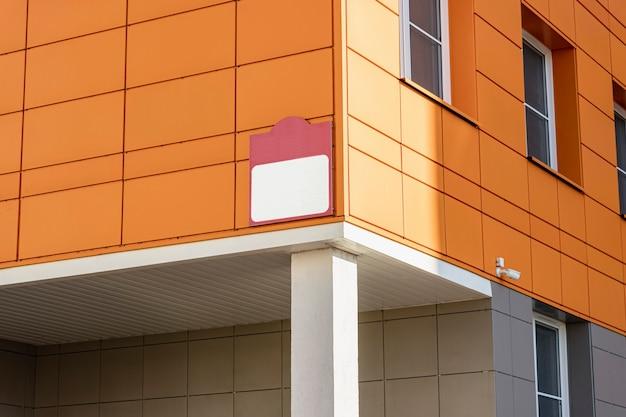 주황색 벽 패널이 있는 현대적인 건물에 사인을 올려보세요. 공공 건물.