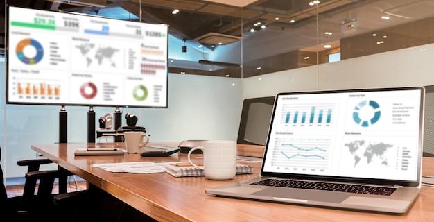 회의실의 테이블에 있는 디스플레이 랩톱 및 tv에서 슬라이드 쇼 프레젠테이션 모의