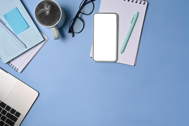 Копируйте смартфон, ноутбук, чашку кофе и чашку кофе на синем фоне.