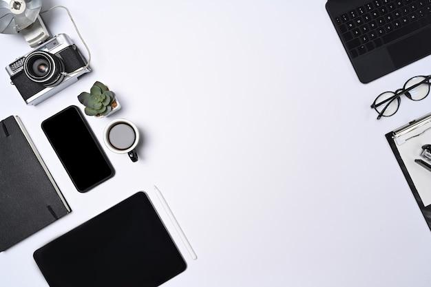 白い背景の上のスマートフォン、タブレット、カメラ、ノートブックをモックアップします。
