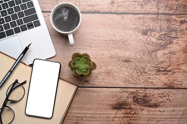 나무 책상에 흰색 화면과 노트북 컴퓨터가 있는 스마트 폰을 비웃으세요.
