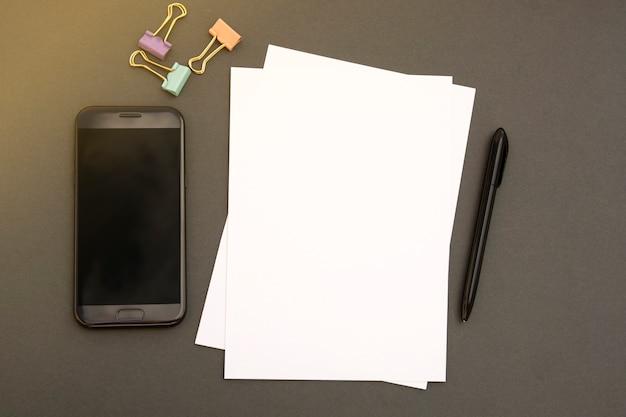 Макет смартфон, пустой перец и офисные аксессуары на сером фоне с копией пространства, плоская планировка. минималистичный стиль рабочего стола.