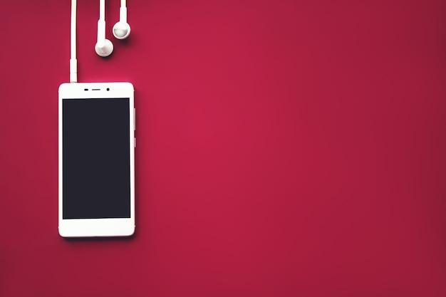 빨간색 배경에 모형 스마트폰입니다. 플랫 레이. 공간을 복사합니다. 평면도. 음악 개념입니다.