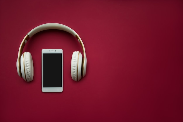 Mock-up smartphone on red background. flat lay. copy space. top view. music concept.