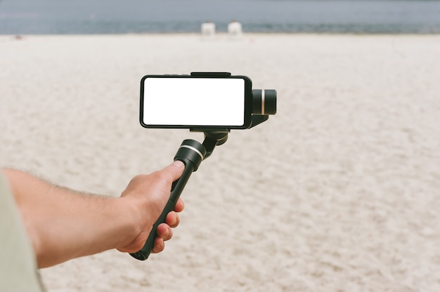 A mock-up of a smartphone on a steadicam in a man's hand. against the backdrop of a beach with sand.