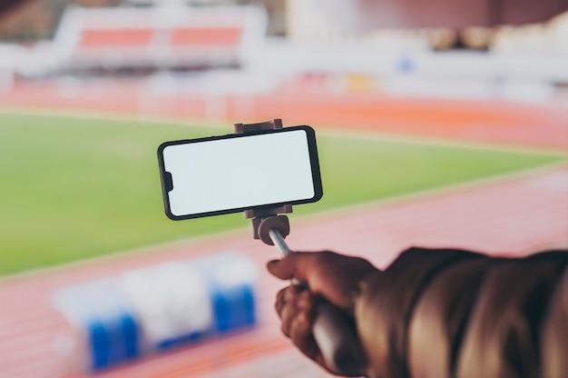 경기장의 배경에 남자의 손에 selfie 막대기로 스마트 폰을 비웃는 다.