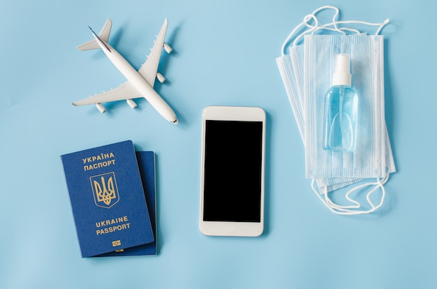 Mock up of smartphone with airplane model, passports of ukraine, face mask and hand sanitizer spray