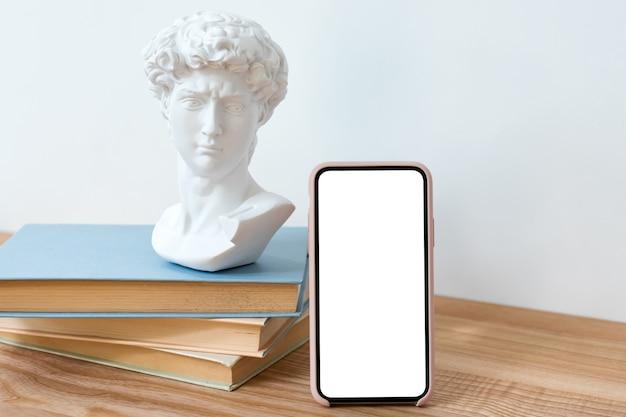 책과 작은 흉상 조각 나무 테이블에 빈 화면 모형 스마트 폰