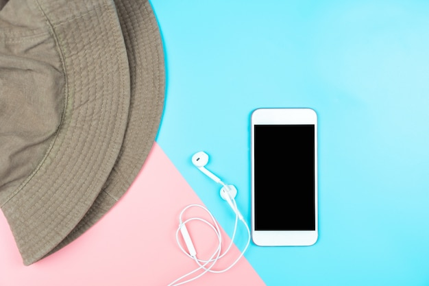 Mock up smartphone with earphones and hat on color background.