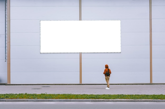 A mock-up of a street billboard against a gray wall with a man walking by.