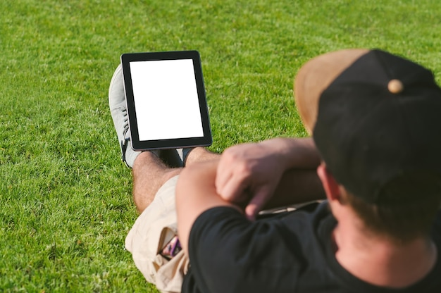 Mock up tablet at the feet of a fitness guy. on the green lawn.