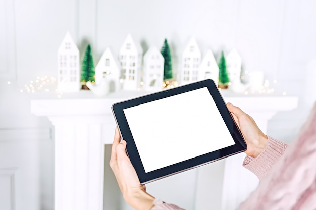 Mock up of the tablet in the hands of the girl on the background, christmas tree with decorative houses festive decoration.