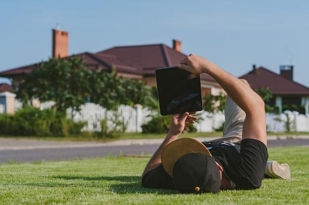 A mock up of a tablet in the hands of a guy in a cap lying on the lawn.