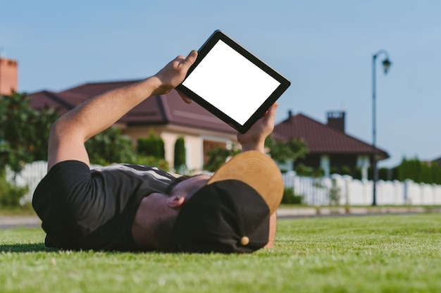 A mock-up of a tablet in the hands of a guy lying on the lawn.