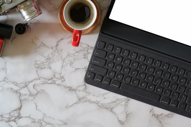 Mock up tablet with smart keyboard, vintage camera on marble workplace