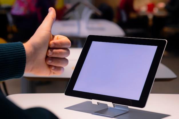 목업 기술. 사업가 흰색 화면으로 디지털 태블릿의 배경에 엄지 손가락을 보여줍니다.