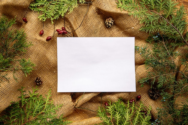 Mock up top view on sheet of paper with festive fir and sackcloth background
