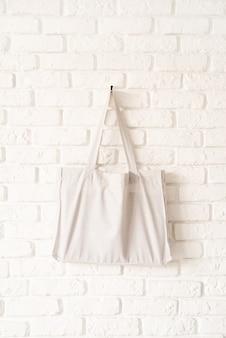 흰색 벽돌 벽 바탕에 흰색 목화 직물의 토트 백을 비웃는 다. 공간 복사