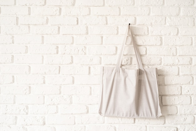Mock up tote bag of white cotton fabric on white brick wall background. copy space