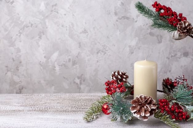 Mock up of two beige vanilla thick christmas candles and wreath of cones, red berries and  branch.