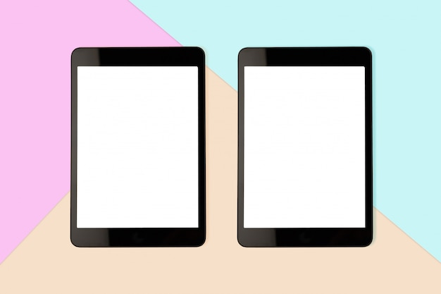 Mock up two digital tablet with blank screen on pastel color background, flat lay photo