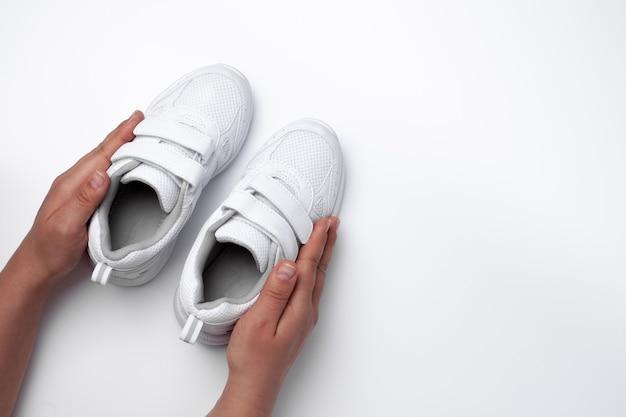 Макет двух рук женщины, держащей детские белые кроссовки с застежками-липучками с пустым промежутком ...