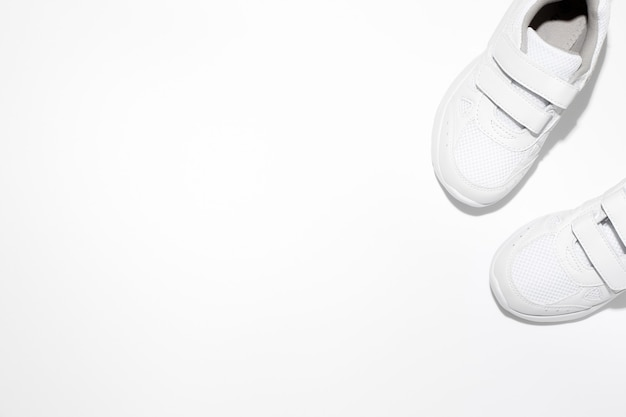 Mock up two white childrens sneakers with velcro fasteners with copy space isolated on a white backg...