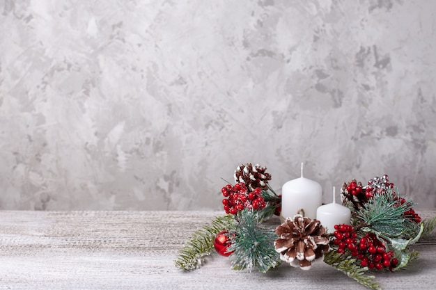 Mock up of two white christmas candles and wreath of  branches, cones, red berries on wooden table.