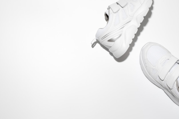 Mock up two white running shoes on the side with free space for text isolated on a white background
