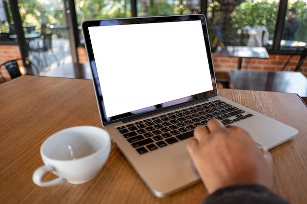 空白のスクリーンコンピューターとラップトップを使用して近代的なコーヒーショップのワークスペース