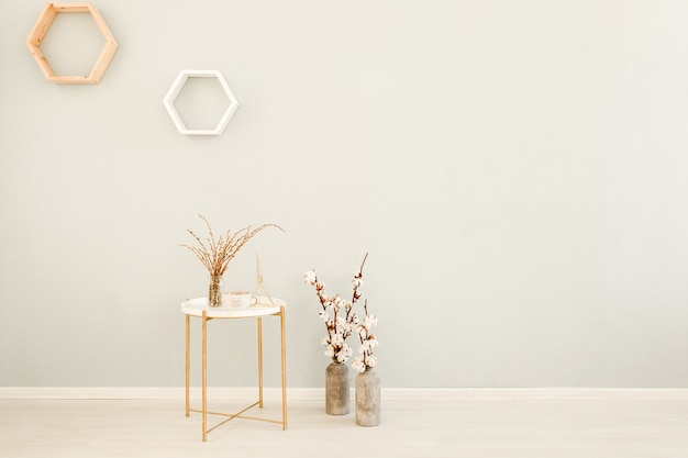 リビングルームの壁をモックアップ、丸いコーヒーテーブルと綿の花瓶を備えた灰色のスカンジナビアスタイルのリビングルーム