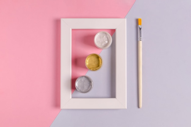 Mock up of a white blank frame with cans of three colors of acrylic paint and a brush for decoration and painting. pink and lilac background, minimalism. selective focus.
