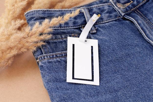마른 팜파스 잔디 장식으로 청바지에 기하학적 로고 슬롯이있는 흰색 빈 종이 태그 또는 레이블을 모의합니다.