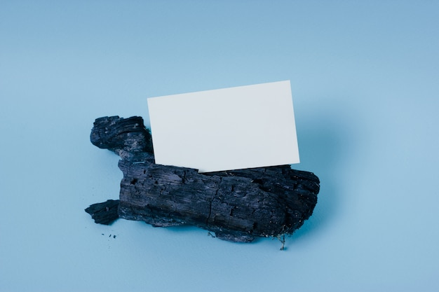 Mock up white business card on a piece of charred wood on blue