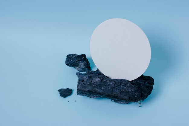 Mock up white card on a piece of charred wood on blue