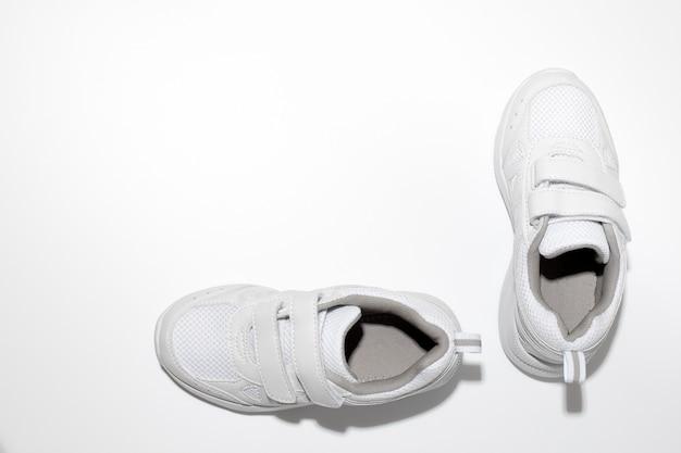 흰색 배경에 격리된 쉬운 신발을 위한 벨크로 패스너가 있는 흰색 어린이 운동화를 조롱
