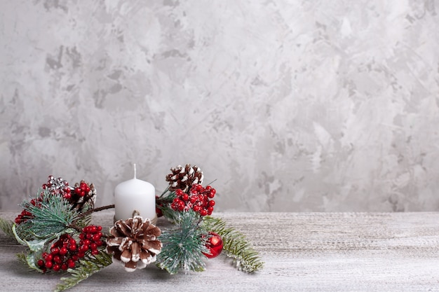 Mock-up of a white christmas candle and a wreath of branches, cones, red berries on a wooden table.