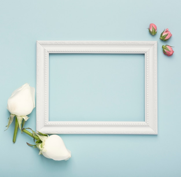 Mock-up white horizontal empty frame with rosebuds on blue background